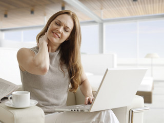 Tired Mid-Adult Woman with Laptop Stretching Neck