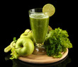 Glass of green vegetable juice and vegetables isolated on black