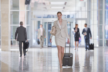 Portrait of smiling businesswoman pulling suitcase in airport
