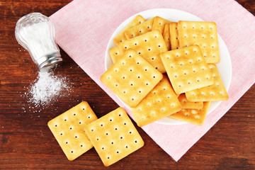 Delicious crackers with salt and napkin on wooden background
