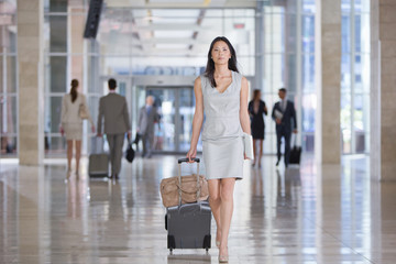 Portrait of confident businesswoman pulling suitcase in airport