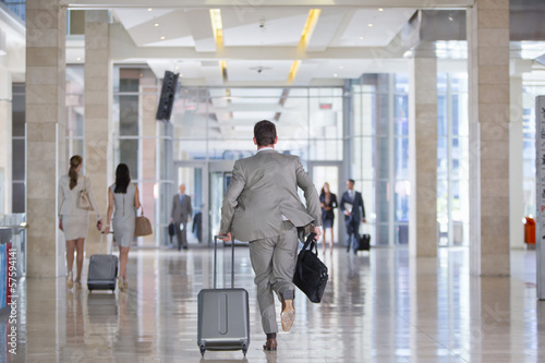 Businessman with briefcase and suitcase running in airport