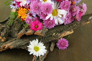 Wildflowers and tree bark on wooden table
