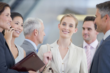 Portrait of smiling businesswoman among co-workers