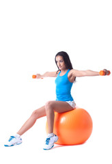 Confident girl exercising with dumbbells in studio