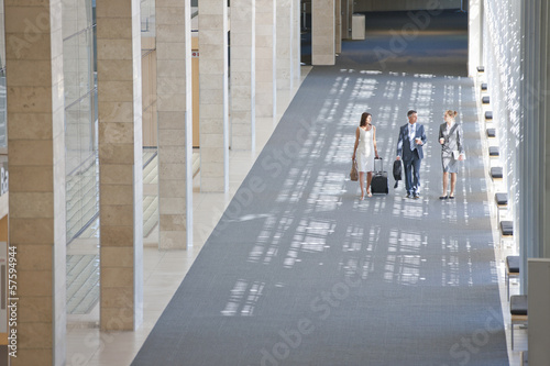 Business people walking in lobby of modern office