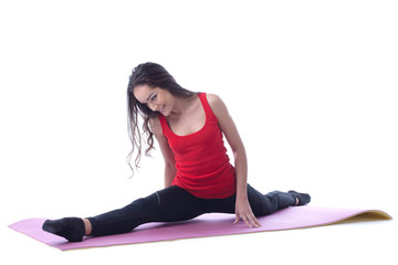 Flexible slim brunette doing split during workout