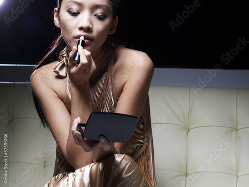Mid-Adult Woman Applying Lipstick