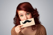 Happy cute girl holding paper with mustache drawing