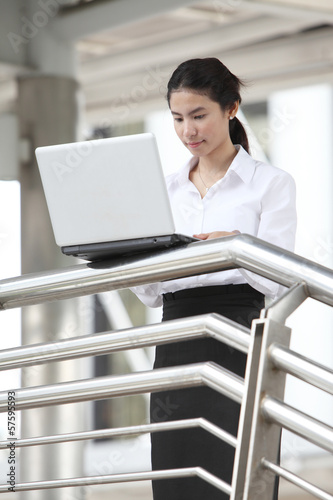 young businesswoman working with her laptop on handrail