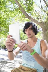 Smiling young man using digital tablet below tree in park