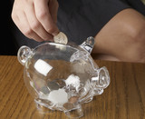 Person Saving Money in Piggy Bank
