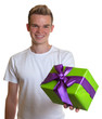 Young man with blond hair showing a gift with ribbon