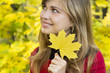 beautiful girl with yellow maple leaves in her hand