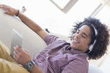Smiling young man wearing headphones and using digital tablet