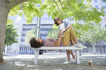 Young couple using digital tablet on urban park bench