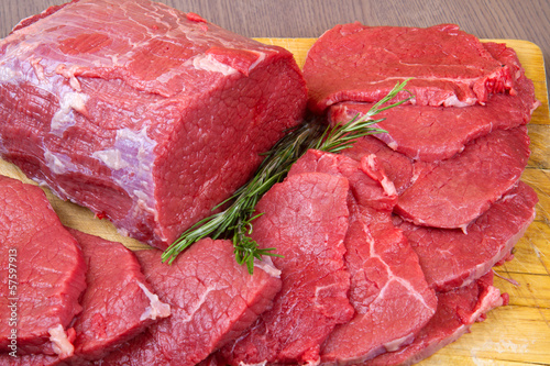 huge red meat chunk and steak isolated over wood background