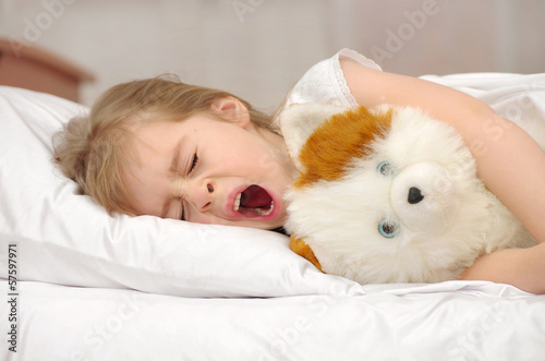 Little girl yawning while lying in bed