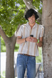 Smiling young man text messaging with cell phone in park