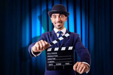 Man with movie clapper on curtain background