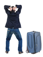 angry young man traveling with suitcas