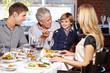 Grandfather feeding grandson in restaurant