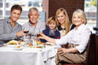 Family clinking glasses in a restaurant