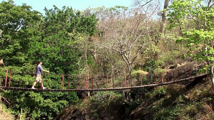 Guy crosses a ravine in the jungle on the rope footbridge.