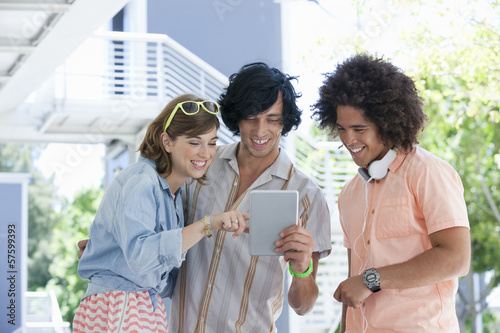Smiling friends using digital tablet