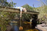 Boy laying on footbridge and dipping fishing net in stream