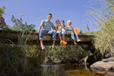 Portrait of smiling family sitting on footbridge over stream
