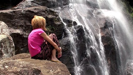 A girl sits on a rock near the waterfall