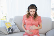 Beautiful calm pregnant woman relaxing listening to music in the