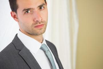 Handsome unsmiling businessman looking at camera
