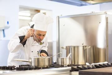 Focused head chef tasting food from ladle