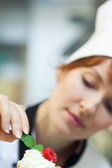Concentrating head chef putting mint leaf on little cake