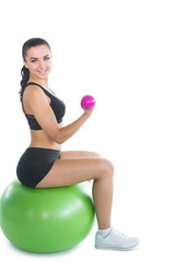 Cheerful active woman sitting on an exercise ball using pink dum