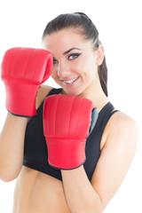 Joyful brunette woman wearing boxing gloves smiling at camera