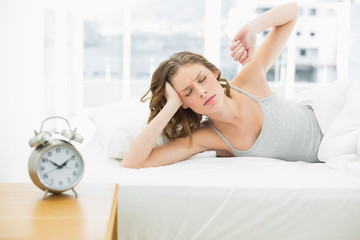 Tired attractive woman stretching out lying in her bed