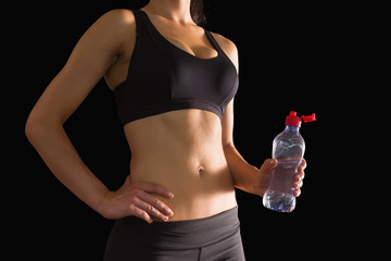 Mid section of slim woman holding a bottle of water