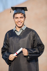 Happy Man In Graduation Gown Holding Certificate On Campus