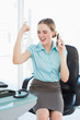 Classy businesswoman on the phone cheering with raised arms