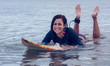 Smiling woman swimming over surfboard in water