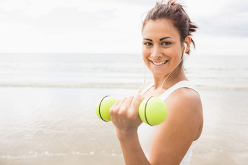 Smiling sporty woman lifting dumbbells on the beach