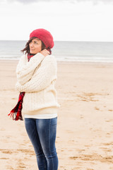 Cute woman in stylish warm clothing at beach