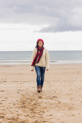 Full length of a woman in stylish warm clothing at beach