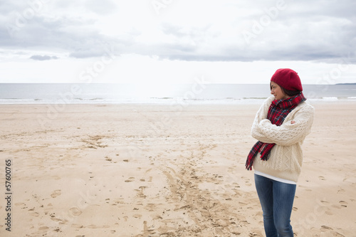 Pretty woman in stylish warm clothing at beach