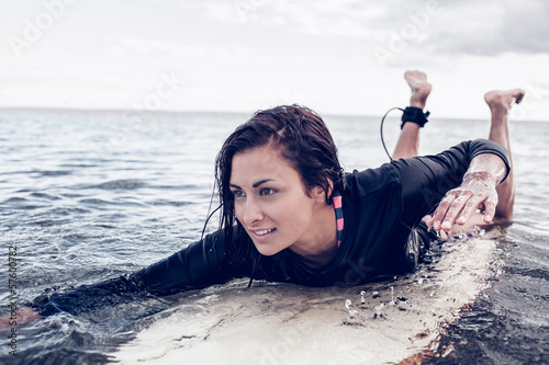 Young woman swimming over surfboard in water