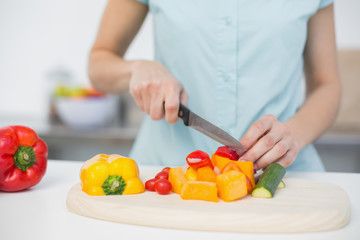 Mid section of young slender woman cutting vegetables