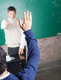 Student Raising Hand To Answer Question In Classroom